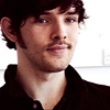 selkieblood: a smirking dark curly short haired man with a bit of a goateeishthing (Eirikr)