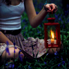 sylvaine: Feminine person sitting in-between grass and flowers at dusk, holding up a lit lantern in front of them. ([gen] ritual)
