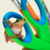 sylvaine: Little green frog sitting on a pair of green-and-blue scissors; yellow pencils in the background. ([gen:craft] art frog!)