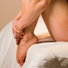 jumpuphigh: The legs of a woman who is sitting on edge of bed with arms wrapped around her legs and her toes curled down. (Toes)