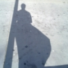 brainwane: A silhouette of a woman in a billowing trenchcoat, leaning against a pole (trenchcoat, shadow)