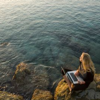 hagar_972: woman with a laptop at a rocky shore looking at the ocean (Default)