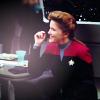 shinyjenni: Janeway sitting at a table, smiling (janeway)