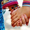frangipani: a close-up photo of two women holding hands (já sei namorar)