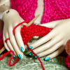 tephra: Close up of doll hands holding knitting in working position. (knitting)