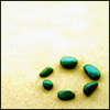 miella: circle of green stones on sand (Default)