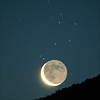 megwrites: A moon rising above a darkened landscape in front of a starry night sky. (moonrise)