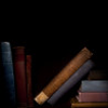 northern: A few books on a shelf, with darkness above them. (reading in the dark)