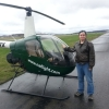 camwyn: Me in a bomber jacket and jeans standing next to a green two-man North Andover Flight Academy helicopter. (helicopter) (Default)
