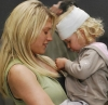 lisaquestions: Starbuck holding a young girl with a bandaged head. (Starbuck)