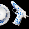 komiiro: A teacup, saucer and a gun, all of which look like porclean with blue flowers on them. (teacup gun)