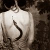 scallion: white woman with snake tattoo on back, early 1900s (protection)
