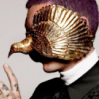 scallion: white man wearing burnished gold bird mask (tatter)