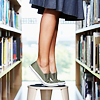 genarti: Knees-down view of woman on tiptoe next to bookshelves (me cheerful)