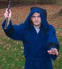 zeeth_kyrah: A man in a deep blue robe looks at the camera, right hand raised and holding a wooden rod, left hand gesturing low. (Magician)