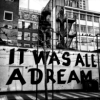 nightdog_barks: Black and white photo of city buildings, with a large graffiti sign saying It Was All a Dream (Dream World)