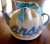 "mathemagicalschema: A teapot with a knitted tea cozy over it. The tea cozy says ""arse"" in a light blue script. (arse teapot)"