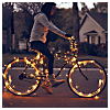 haleskarth: A person riding a bicycle with fairy lights woven into the spokes. (Lights entangled.)