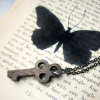 lemniscatic: a key and the shadow of a butterfly on a book. ([default]) (Default)