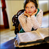 recessional: a young girl with light brown skin and dark hair has a backpack and is leaning her chin in her hands (writing; traceuse)