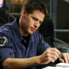 skieswideopen: Cameron Mitchell from SG-1 sitting at a table holding a pen (SG: Cam paperwork)