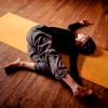 rydra_wong: A woman (yoga teacher Jess Glenny) lies on the floor in a reclining twist. (yoga -- twist)