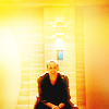 amihan: christopher eccleston as the ninth doctor, seated and smiling, against an orange-yellow background ([doctor who] nine (yellow))