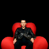 amihan: christopher eccleston as the ninth doctor in 'doctor who' seated on a red sofa, looking confused ([doctor who] nine (reality tv))