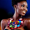timeasmymeasure: black woman smiling widely, looking to the right; she's wearing a heavy brightly beaded necklace (stock: swag smile)