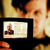 januar: Eleven from Doctor Who holding up a library card that has the First Doctor on it ([dw] library card)