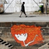 flaneurs: A person walking along an urban riverbank, above graffiti of a cartoon person with white skin and long wavy red hair. (flaneurs)