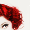 commodorified: cropped pic of woman with short curly red hair looking up  impishly from the lower left corner (femme)