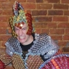 aaaaaaaagh_sky: A snarling man wearing a helmet, armor, and shield made entirely out of multicolored bottlecaps (PA- Captain Caps)