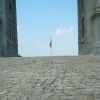 aaaaaaaagh_sky: Grey cobblestones in the foreground, the sides of a grey stone arch framing blue sky, and a distant flagpole (PA - Valley Forge, cobblestones, flagpole, inside the arch)