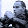 smilingslightly: F1 driver Lewis Hamilton gazing into the middle distance, hands clasped and touching his chin. Blue monotone scheme. (lewis_blue)