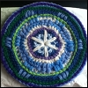 curiosity: A circular bit of crochet in blues and greens with white accents and some lavender. Makes a nice bit of wall art. (Picto: Crochet Mandala)