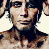 fanatic_os: hollow-faced & eyed man, visibly dirtied and bruised, face on, grey stubble, hands cut off holding something to his head (post-death: crowned)
