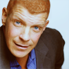 bigraudr: big redhead man with blue eyes, slightly down angle on his buzzcut, neutral, approachable expression (Default)