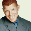 bigraudr: big redhead man with blue eyes, slightly down angle on his buzzcut, head tipped a little left, friendly smile (friendly; smile; approachable; encouragi)
