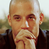 thirteen_pillars: An olive-skinned bald man (Vin Diesel) looks at the camera. His hands are linked and propped in front of his mouth. (Default)