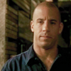 thirteen_pillars: An olive-skinned bald man (Vin Diesel) looks slightly left of camera. He looks dubious. (Dubious)