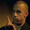 thirteen_pillars: An olive skinned bald man (Vin Diesel) holds up a finger, telling someone off camera to pause or be quiet. (Hush)