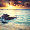 safekeeper: Amber sunset over a turquoise sea, large rocks partially submerged in the foreground. (sea)