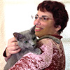 zlabya: Photo of an auburn-haired woman with glasses holding a Russian Blue cat (BethIvan)