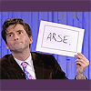 rhivolution: David Tennant, looking frustrated and holding up a sign that says 'ARSE' (u r a wanker: so says David Tennant)