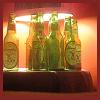 nkyinkyin: a cluster of empty yuengling lager bottles under a lamp. ([4] freyresson)