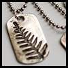 nkyinkyin: a photo of a dogtag that has a fern leaf stamped on it instead of a name. (tags; identity; naming)