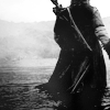 meneltarma: black and white image of a man in medieval clothes wading into a river from behind (Default)