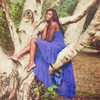 bilqis: black woman dressed in blue in a tree (Default)