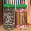 undeleterious: two sambal oelek chili paste jars filled with black and pink paper stars, in front of some animorphs books on a shelf (primary)